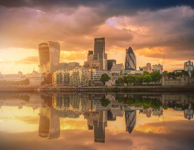 Wolkenkratzer der stadt von london über der themse bei sonnenuntergang in england.