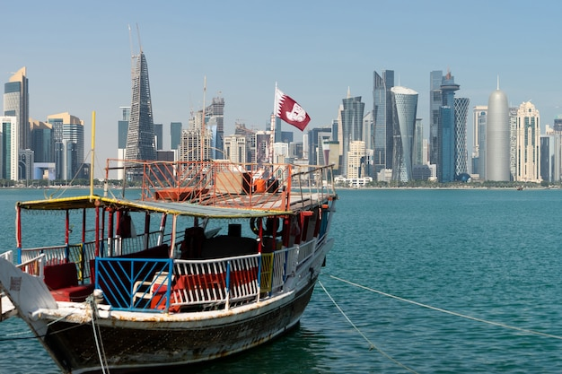Wolkenkratzer im stadtzentrum mit wasser und bootsvordergrund von doha, katar.