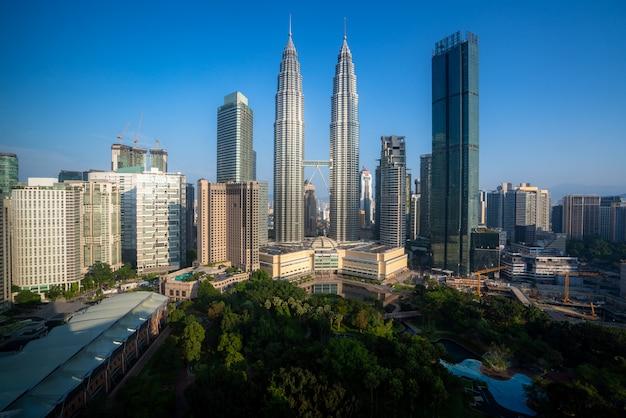 Wolkenkratzer und grünflächenpark der stadt kuala lumpur mit schönem himmelstag im geschäftsviertel der innenstadt in kuala lumpur. malaysia.