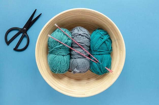 Wolle und stricknadeln im korb