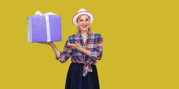 Wollen sie geschenk? glückliche schöne moderne oma mit weißem hut und kariertem hemd, die eine große geschenkbox mit einem zahnigen lächeln hält, die hand zeigt und die kamera betrachtet. studioaufnahme, gelber hintergrund