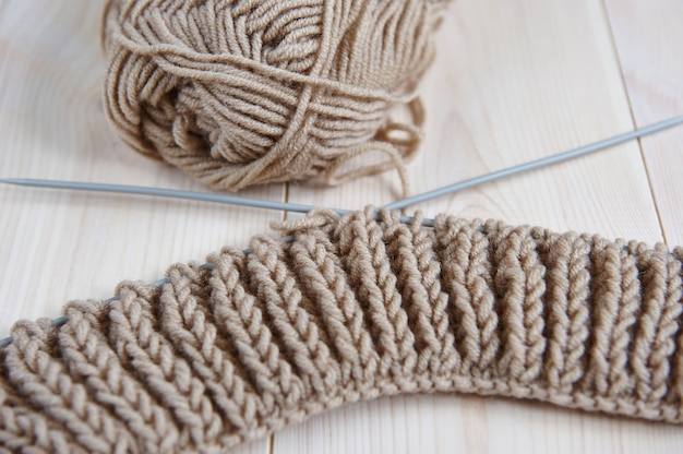 Wollfaden mit stricknadeln zum handstricken auf einem holztisch
