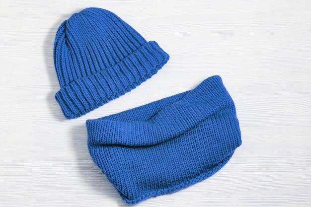 Wollgestrickte kleidung, blaue mütze und schal. winterkleidung der warmen frau auf weißem holz