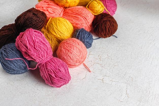 Wollknäuel in verschiedenen farben mit stricknadeln.