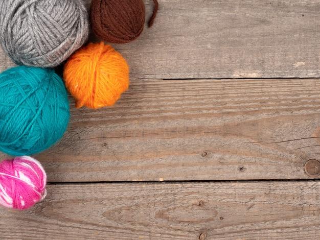 Wollknäuel in verschiedenen farben und größen liegen auf einer natürlichen holzoberfläche. draufsicht. speicherplatz kopieren.