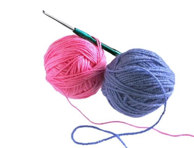 Wollknäuel und häkelnadel isoliert auf weißem hintergrund. kugeln aus rotem, blauem wollgarn und stricknadeln.