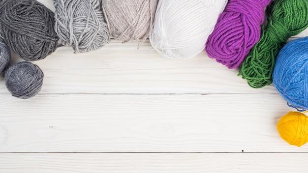 Wollknäuel zum stricken liegen auf einer weißen oberfläche. draufsicht. speicherplatz kopieren.