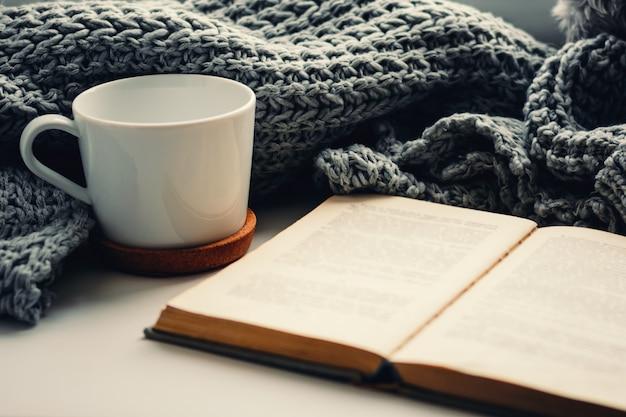 Wollschal, eine tasse tee und ein buch auf der fensterbank. hygge und gemütliches herbstkonzept