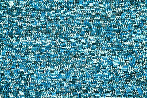 Wollschal oder pullover textur nahaufnahme. blauer gestrickter jerseyhintergrund mit einem reliefmuster. zöpfe im maschinenstrickmuster