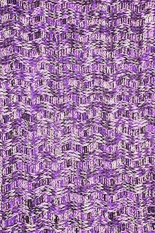 Wollschal oder pullover textur nahaufnahme. ultraviolett gestrickter jersey-hintergrund mit reliefmuster. zöpfe im maschinenstrickmuster