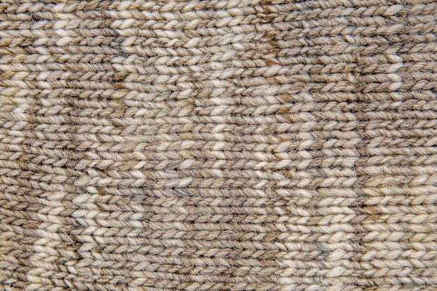Wollschal textur nahaufnahme. gestrickter jersey-hintergrund mit reliefmuster. zöpfe im maschinenstrickmuster