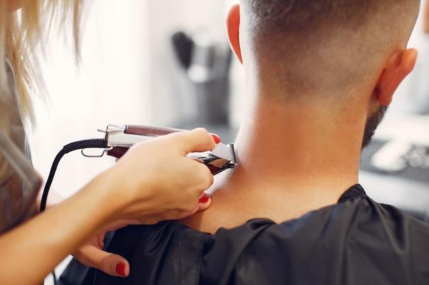 Woma, der den bart des mannes in einem friseursalon rasiert
