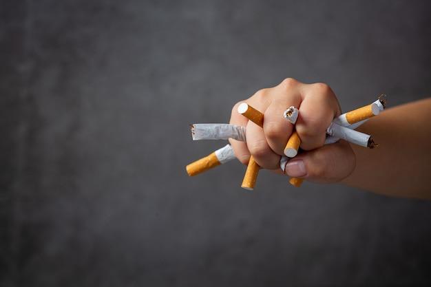 Womanan hand hält und zerstört zigaretten auf der dunklen oberfläche. welt kein tabak tag konzept.