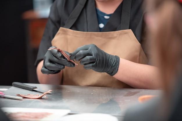 Womans hände, die eine sardelle säubern frau, die mit fisch arbeitet und sardellenfilets herstellt