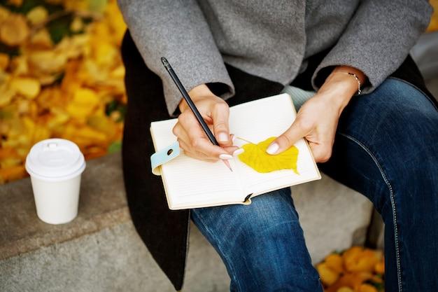 Womans hände nahaufnahme halten papiernotizbuch und bleistift und etwas schreiben oder skizzieren