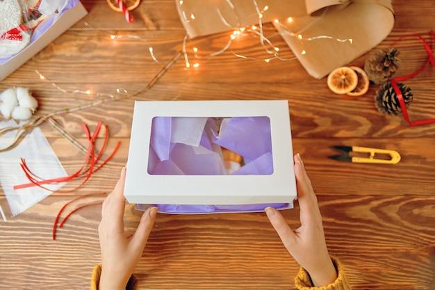 Womans hände öffnen geschenkbox mit weihnachtsplätzchen lebkuchen mit zuckerguss festliche süßigkeiten tannenzapfen dr...