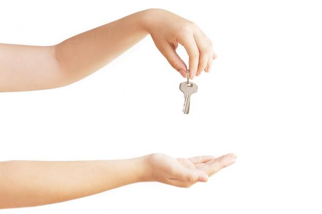 Womans hand mit metallschlüssel. schlüssel in der hand auf weißem hintergrund. isoliert auf weiß