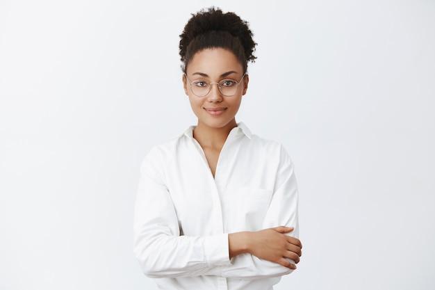 Womit kann ich ihnen behilflich sein. charmante freundlich aussehende afroamerikanerin in brille und weißem hemd, händedrucke auf brust. höflich lächeln, kunde zuhören, auf veränderung im restaurant warten