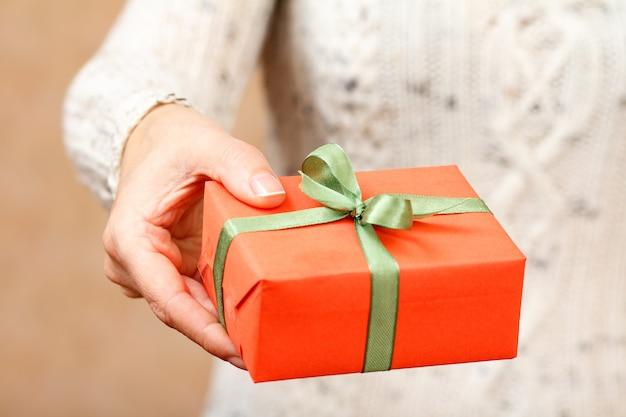 Wooman, der eine geschenkbox mit einem grünen band in der hand hält. geringe schärfentiefe, selektiver fokus auf die box.