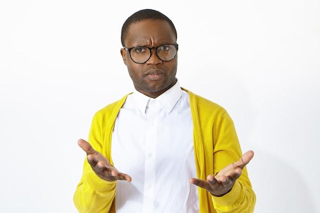 Worauf wartest du. horizontale aufnahme eines stirnrunzelnden empörten jungen afroamerikanischen mannes in einer stilvollen brille, die emotional gestikuliert, empörung ausdrückt, einen verwirrten blick hat und ratlos ist