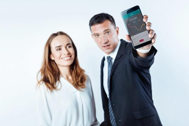 Worauf wartest du. selektiver fokus auf einem bildschirm eines smartphones mit einer online-brieftasche, die von einem männlichen geschäftsmann gehalten wird, der neben seinem kollegen steht und prahlt.