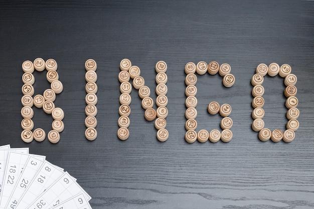 Word bingo aus holzfässern. schwarzer holztisch. lotto