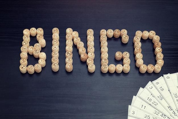 Word bingo aus holzfässern. schwarzer holztisch.