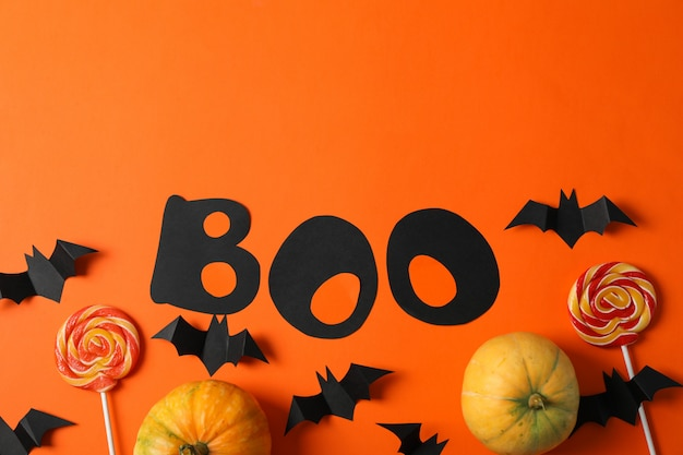 Word boo, süßigkeiten, dekorative fledermäuse und kürbisse auf orange tisch, kopieren raum