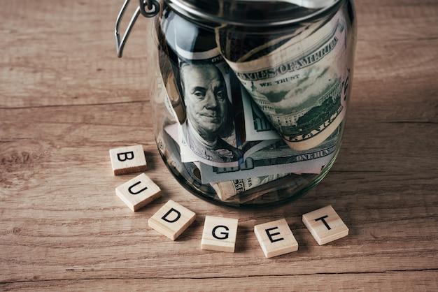 Word-budget und dollarbanknoten im glas