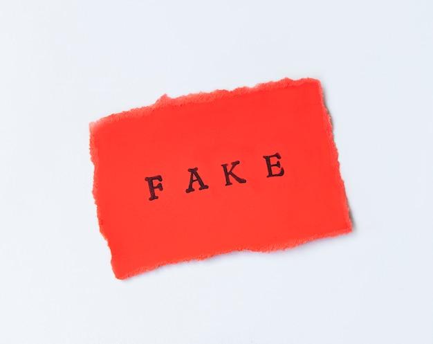 Word fake geschrieben auf zerrissenem papier