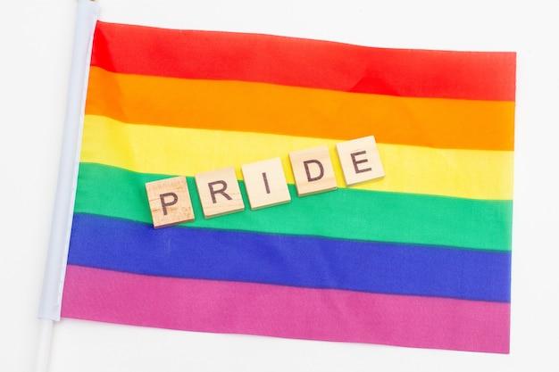 Word pride aus holzwürfeln auf einer lgbt-stolzfahne.