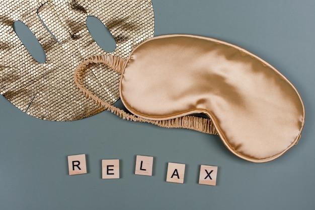 Word relax mit goldener schlafender augenmaske und kosmetischer gesichtsmaske, flug- und reisekonzept