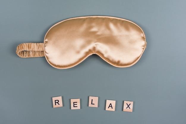 Word relax und goldene schlafende augenmaske, draufsicht, gute nacht, flug- und reisekonzept