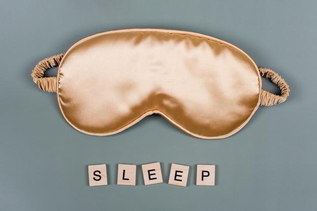 Word sleep und goldene schlafende augenmaske, draufsicht, gute nacht, flug- und reisekonzept