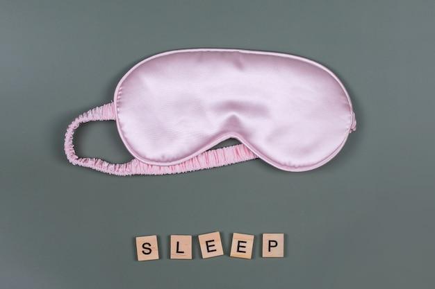 Word sleep und rosa schlafende augenmaske, draufsicht, gute nacht, flug- und reisekonzept