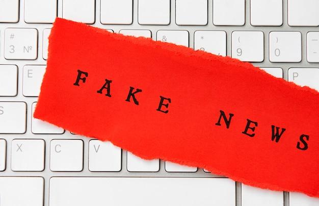 Words fake news auf zerrissenem papier geschrieben