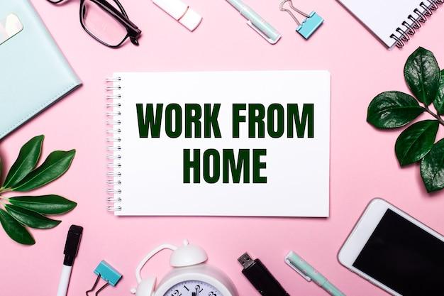 Work from home ist in einem weißen notizbuch auf einer rosa oberfläche geschrieben, umgeben von geschäftsaccessoires und grünen blättern