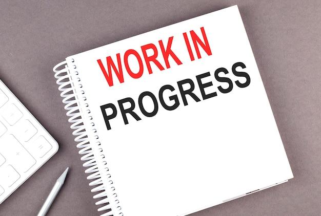 Work in progress text auf dem notebook mit taschenrechner und stift
