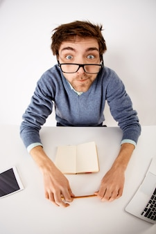 Workaholic-, geschäfts- und bürokonzept. oberwinkelaufnahme des mannes, der bei der arbeit verrückt wird