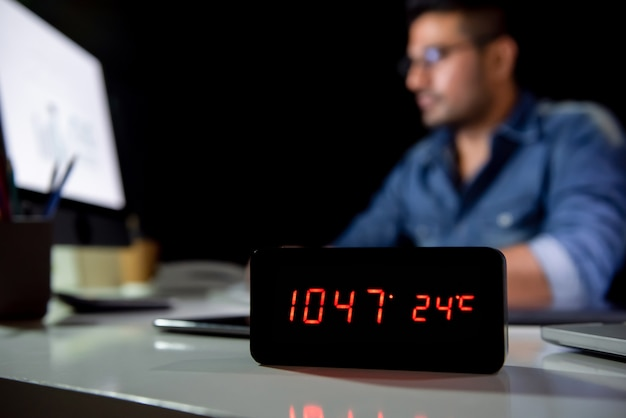 Workaholic-mann, der spät über nacht nachts im büro arbeitet