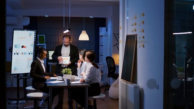 Workaholic überarbeiteter geschäftsmann, der die unternehmensstrategie mit tablet für präsentationen erklärt, die überstunden im besprechungszimmer spät in der nacht machen