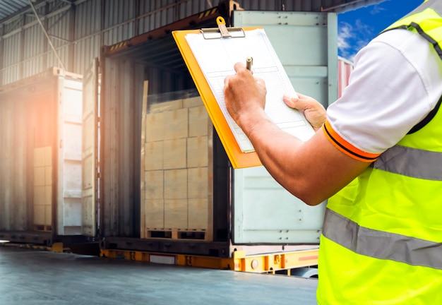 Worker holding clipboard ist die kontrolle des ladens der paketbox in die frachtcontainer-lagerlogistik