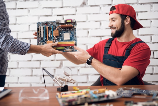 Worker of computer service erhält ein motherboard.