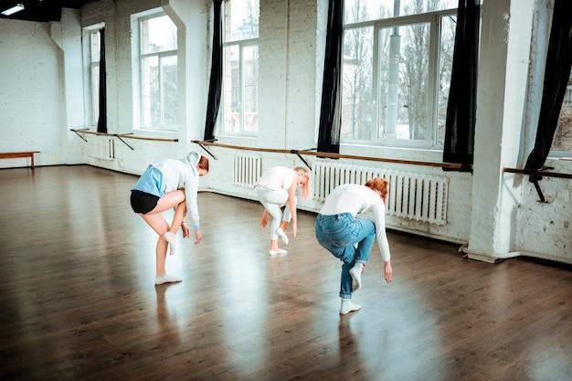 Workout in bearbeitung. rothaariger tanzlehrer in blue jeans und zwei studenten, die beim tanzen im studio involviert aussehen
