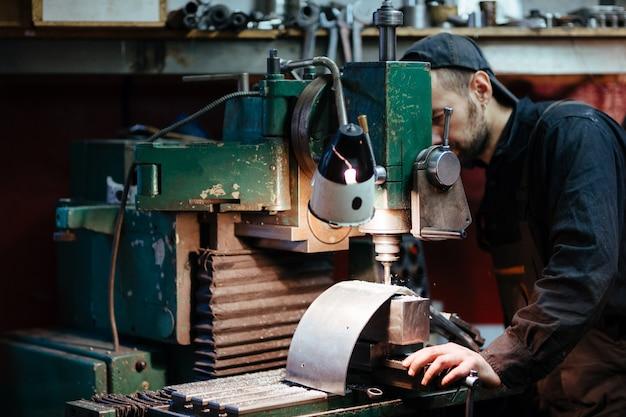 Workshop worker bohren von metallteilen