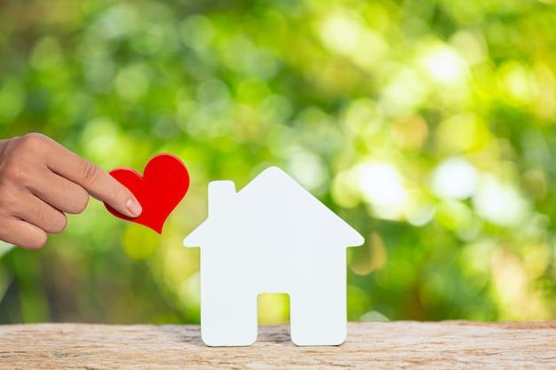 World habitat day, nahaufnahmebild eines modellhauses und hand, die papierherz hält