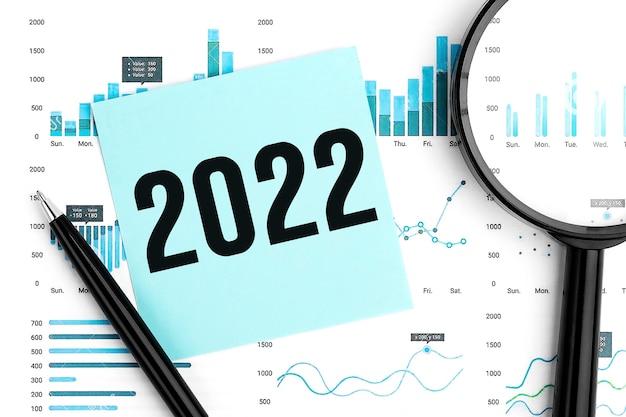 Wort 2022 auf aufkleber. lupe, stift und diagramme und grafiken draufsicht. geschäfts- und statistisches konzept auf weißem hintergrund.