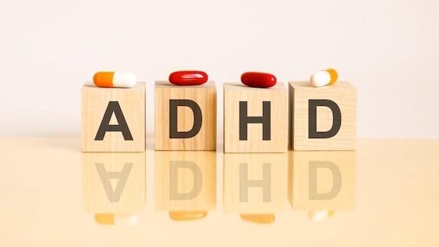 Wort adhd besteht aus holzwürfeln auf gelbem hintergrund mit pillen. medizinisches konzept der behandlung, prävention und nebenwirkungen. adhs – kurz für aufmerksamkeitsdefizit-hyperaktivitätssyndrom
