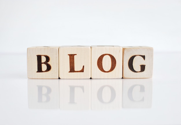 Wort blog gemacht mit holzwürfeln, weißer hintergrund mit reflexion.