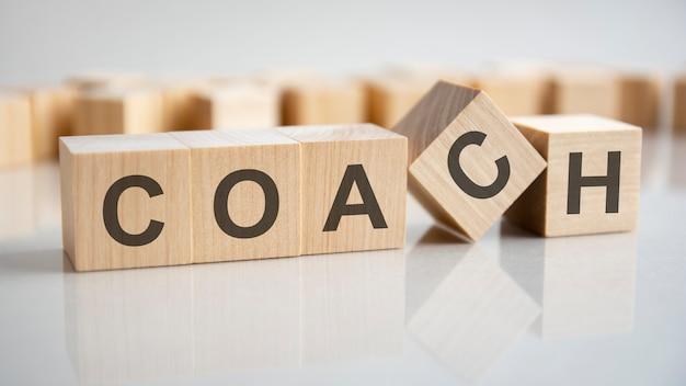 Wort coach auf holzwürfeln, grauer hintergrund. reflexion auf der verspiegelten oberfläche des tisches. selektiver fokus.